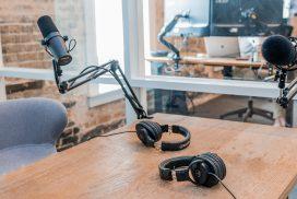 Studio, jossa pöytä, kaksi mikkiä ja kahdet kuulokkeet.
